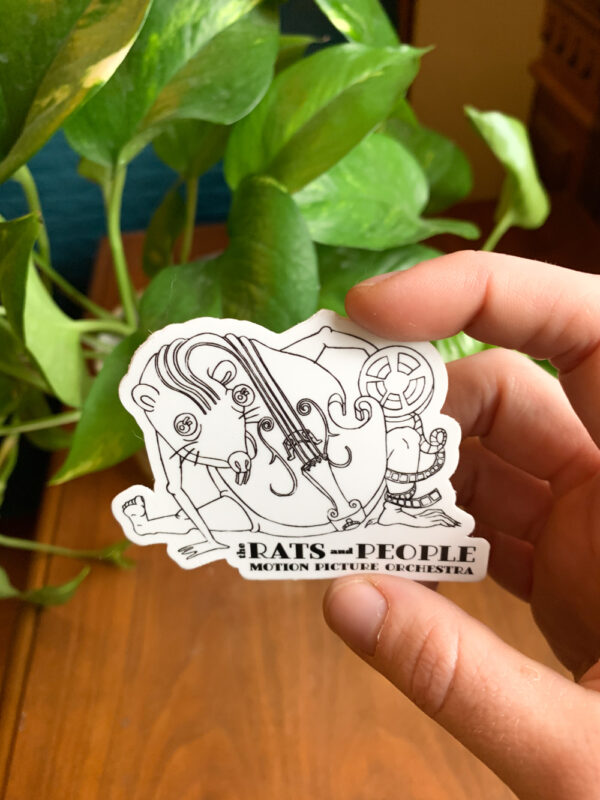 Small, white cello rat sticker held in front of a green viney plant