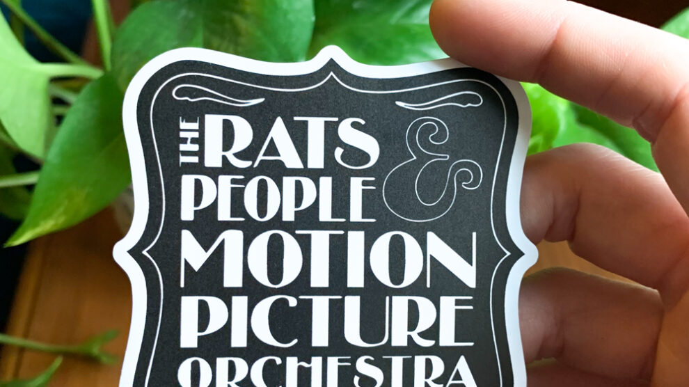 Rats and People Magnet being held in front of a green viney plant